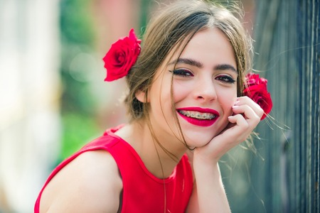 Cute girl or pretty woman with red lips, stylish makeup on adorable young face, healthy skin and roses in brunette hair posing on sunny day outdoors on blurred background. Beauty, health. Summer