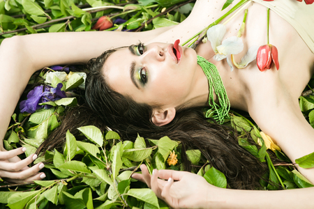 adn: beauty and fashion, spa adn relax, woman with fashionable makeup in green beads with tulip flowers laying on green leaves in spring or summer on natural background