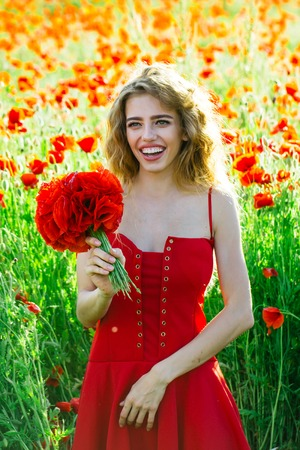 pretty woman or happy smiling girl with long curly hair in red dress hold flower bouquet in field of poppy seed with green stem on natural background, summer, spring, drug and love intoxication, opium