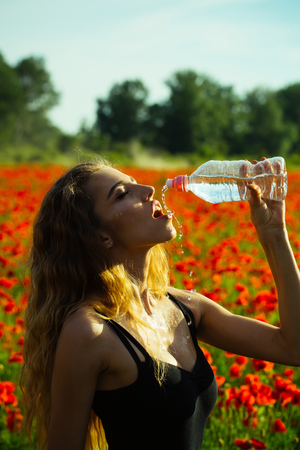 sexy girl with long hair drink water from plastic bottle in flower field of red poppy, summer, drug and intoxication, opium, refreshment and relax, sport and fitness, healthcare and thirst, youth