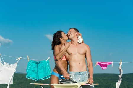 undergarments: young sexy couple in love or family of woman with buttocks and muscular athletic man kiss at iron, ironing board with clothesline rope with underwear on sunny blue sky background, household and summer