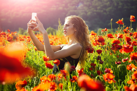 girl with long curly hair in black vest making selfie photo by mobile phone in flower field of red poppy seed with green stem on natural background, summer, spring, drug and love intoxication, opium