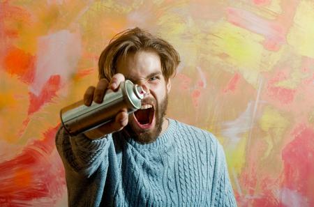 Kunstenaar of schilder met baard en blond haar, stijlvolle kapsel met een spuitverf of fles in grijze trui op roze en gele abstracte muur. Straatkunst, graffiti cultuur Stockfoto