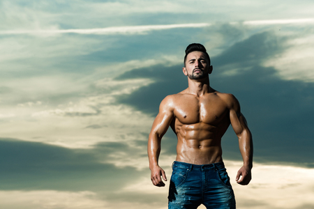sexy man with muscular wet body and strong torso of bearded bodybuilder athlete in jeans posing with bare chest and belly outdoor on sunset sky background, copy space