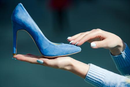 履物。背景をぼかし、ファッション、美容、ショッピング、プレゼンテーション、シンデレラに女性の手でグラマー靴ブルー色スエード 写真素材