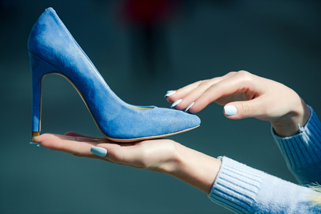 footwear. glamour shoe blue color suede on female hand on blurred background, fashion and beauty, shopping and presentation, cinderella