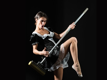 pretty sexy girl or maid in housemaid uniform apron dancing with mop as guitar on black background, housekeeping and cleaning Foto de archivo