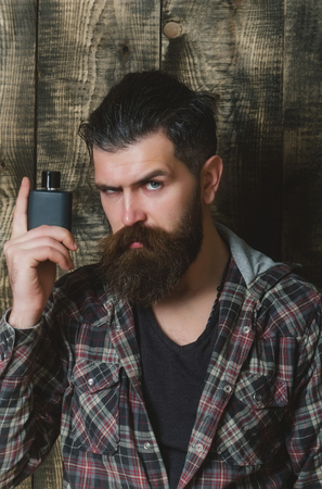 man or bearded caucasian hipster with grey hair, long beard and moustache posing with black perfume or cologne bottle on wooden background. Male fragrance and perfumery. Cosmetics
