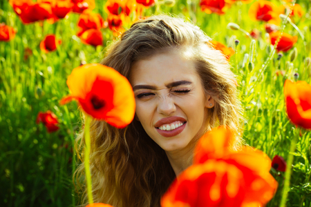 woman or happy winking girl with long curly hair hold flower in field of red poppy seed with green stem on natural background, summer, spring, drug and love intoxication, opium Stock Photo