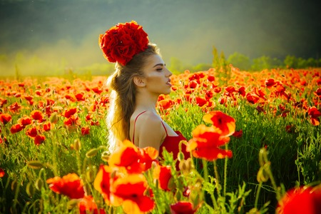 beautiful woman on poppy field with long hair and bouquet