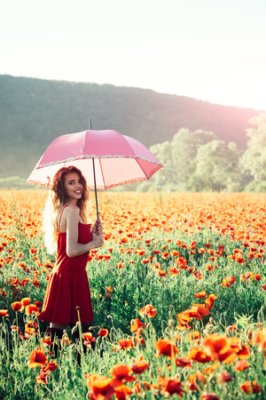umbrella pink color at pretty happy girl with long curly hair in red dress in field of poppy seed flower on green stem on natural background, summer, drug and love intoxication, opium