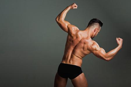 男筋肉ボディと強力な上腕二頭筋と上腕三頭筋、灰色の背景上の下着のパンツでボディービルダー選手のスポーツとトレーニング、コピー スペース