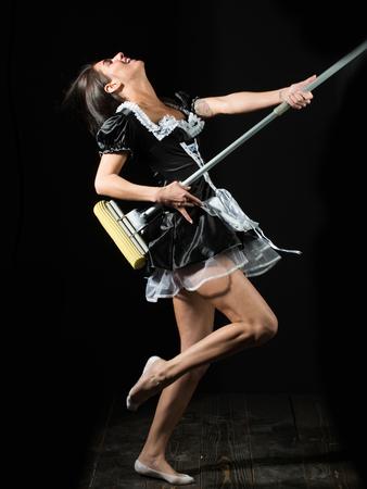 Housekeeping en schoonmaak, mooie sexy meisje of meid in housemaid uniforme schort dansen met mop als gitaar op zwarte achtergrond Stockfoto