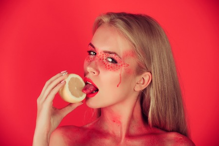 lemon in hand of woman with creative fashionable makeup on face hold and lick fruit in hands on red background, beauty and fashion, allergy, healthcare, vitamin, vegetarian and dieting