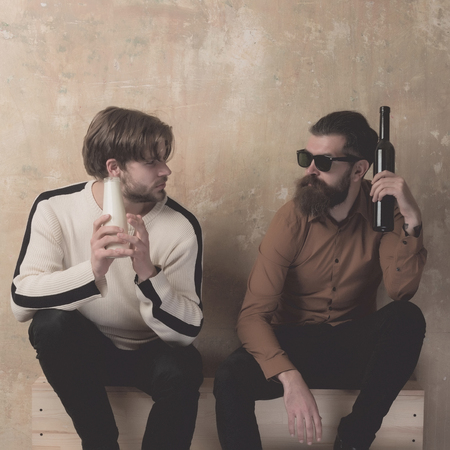 friendship of stylish friends talking and drinking on beige wall. Handsome model in sweater with milk or yogurt bottle and bearded man in sunglasses with stainless hip flask. Healthy lifestyle Stok Fotoğraf