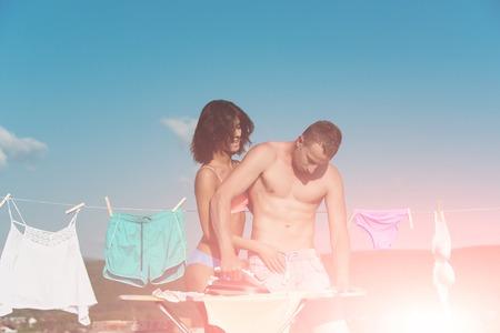 가족 또는 젊은 섹시 한 부부 엉덩이와 근육 질의 운동 남자와 여자의 사랑 철 분, 화창한 파란 하늘 배경, 가정과 여름에 속옷과 함께 빨랫줄로 다림