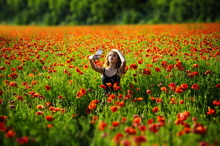 flower field of red poppy seed with green stem and girl with long curly hair in black vest making selfie photo by mobile phone on natural background, summer, spring, drug and love intoxication, opium