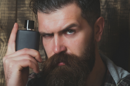 perfume or cologne bottle bearded man or brutal caucasian hipster with long beard and moustache on serious face on wooden background. Male fragrance and perfumery. Cosmetics
