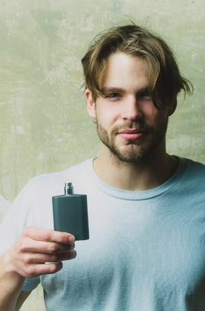 macho man with blond hair, stylish haircut posing with black perfume or cologne bottle in white tshirt on grey background. Male fragrance and perfumery. Cosmetics, beauty Reklamní fotografie