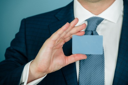 hand holding blank bank or business card in formal suit with stylish tie on blue background. Economy, credit, ecash, banking, ethics and information