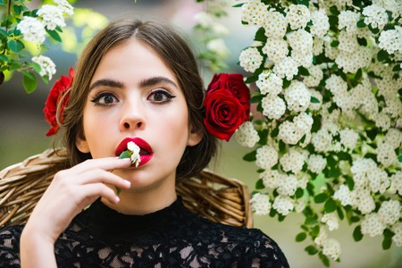 surprised girl or cute woman with white flower in hand and stylish makeup on adorable face, with red roses in brunette hair, hairstyle, sitting on floral environment. Spring, summer. Nature, beauty Zdjęcie Seryjne