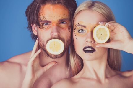 vitamine: man and girl with creative fashionable makeup on face hold lemon fruit on blue background, beauty and fashion, allergy, healthcare and vitamin, vegetarian and dieting, couple in love Stock Photo