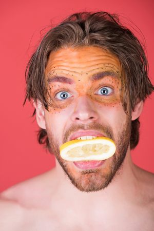 man with creative fashionable makeup on surprised face hold lemon fruit in mouth on red background, beauty and fashion, allergy, healthcare and vitamin, vegetarian and dieting
