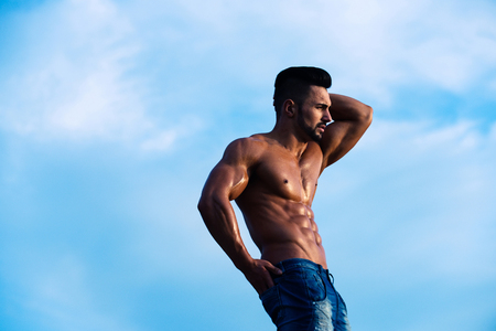 muscular man with muscle torso sunny day on blue sky background, summer vacation, copy space Stock Photo