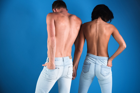 gentle married couple in jeans, back view, lovers man and woman with buttocks in blue pants, naked sexy couple on blue background