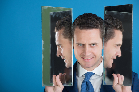 smiling man with beard and self reflection in mirror on blue background, copy space