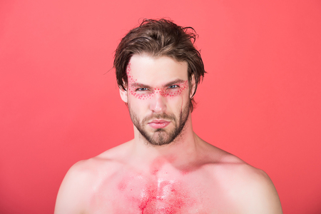 bodyart: handsome man with creative fashionable makeup on face on red background, beauty and fashion, allergy Stock Photo