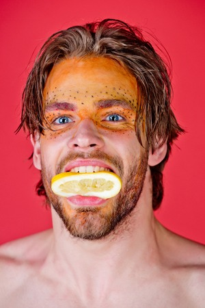 vitamine: guy with creative fashionable makeup on smiling face hold lemon fruit in mouth on red background, beauty and fashion, allergy, healthcare and vitamin, vegetarian and dieting