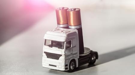 おもちゃのトラックや白い背景の 2 つの AA 電池電源装置要素を運ぶ車。輸送、配送、出荷。エネルギー、電気料金、技術、アキュムレータ