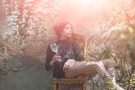 wine glass in hand of woman or fashion model sitting on chair in sunny yard on outdoor wall. Alcohol drinking. Enjoying life. Holiday celebration. Spring or summer bloom 版權商用圖片