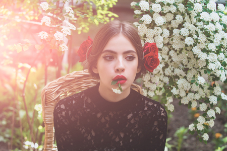 Cute girl or pretty woman with white flower in mouth with red lips, stylish makeup on thoughtful face and roses in brunette hair on floral environment. Spring and summer. Nature beauty Stock Photo