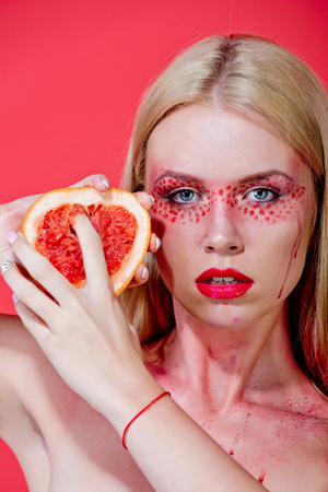 pretty blonde woman with creative fashionable makeup on face hold grapefruit fruit in hands on red background, beauty and fashion, allergy, healthcare and vitamin, vegetarian and dieting Stock Photo