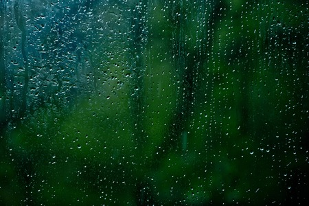 wet glass of window with water drops on blurred green background Stock Photo