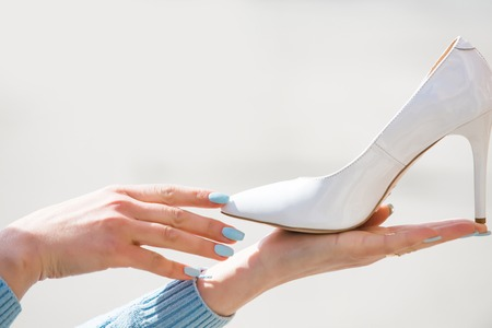 shoe. footwear white color leather on female hand on blurred background, fashion and beauty, shopping and presentation, cinderella, copy space Stock Photo