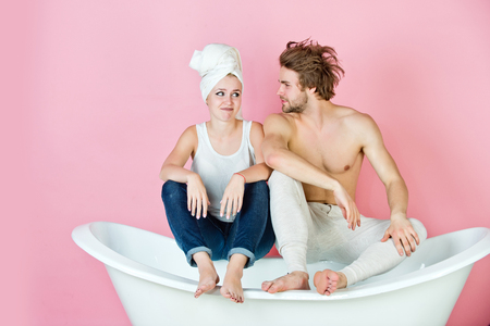 couple in love of muscular man and woman with towel sitting on white bathtub on pink background, family, relationship and romance, spa and beauty, relax and hygiene, healthcare