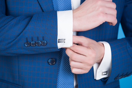 hand fixing elegant silver cufflink on white shirt cuff on sleeve of navy formal suit with fashionable buttons on blue background. Business fashion and jewelry
