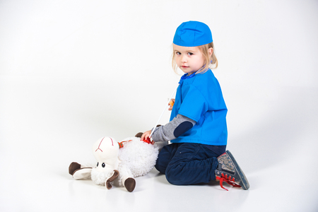 doctor kid or small boy in blue uniform playing vet with toy animal of donkey in medical hospital isolated on white background, medicine and healthcare, copy space