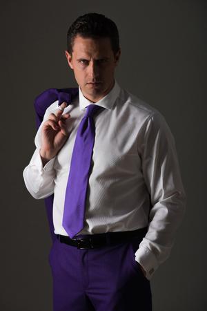 ビジネスマンやファッショナブルな白いシャツ、青いネクタイと灰色の背景上の肩にジャケットでポーズをとって成功した男マネージャー。ビジネ 写真素材