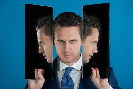 2 つのミラーで 3 つの顔を持つ男。ハンサムな実業家または赤の背景に青いネクタイのマネージャーの反射.機敏なビジネス。男性の美しさ