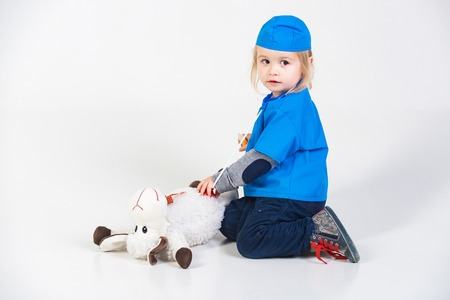 nurse hat: vet kid or small boy in blue uniform playing doctor with toy animal of donkey in medical hospital isolated on white background, medicine and healthcare, copy space Stock Photo