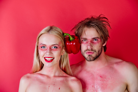 vitamine: man and woman with creative fashionable makeup on happy face with sweet bell pepper or paprika on red background, beauty and fashion, healthcare and vitamin, vegetarian and dieting, heart, couple in love Stock Photo