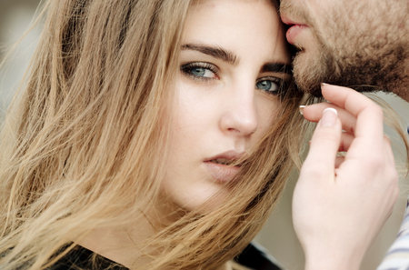 Cute girl or pretty woman with fashion makeup on adorable face and stylish long hair. Sensual kiss of male lips with unshaven beard and moustache. Love and tenderness