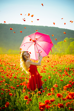woman with long curly hair in red dress hold pink umbrella in field of poppy seed flower on green stem with petal in sky on natural background, summer, drug and love intoxication, opium
