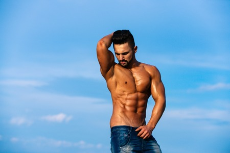 muscular man. man with muscular wet body and strong torso of bearded bodybuilder athlete in jeans posing with bare chest and belly sunny outdoor on blue sky background, copy space