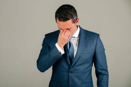 男は、ハンサムな実業家やスタイリッシュな髪、ファッショナブルなブルーのフォーマルなスーツで散髪のボス感頭痛ホワイト シャツ、灰色の背景