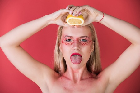 squeezing: pretty blonde woman with creative fashionable makeup on face hold lemon fruit in hands on red background, beauty and fashion, allergy, healthcare, vitamin, vegetarian and dieting Stock Photo
